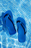 Flip-flops. A pair of flip-flops floating on the water on a swimming pool stock photos
