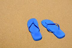 Flip-flops. A pair of flip-flops floating on the sand on a beach stock image