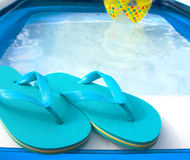 Flip flops. And beach ball by the pool royalty free stock photos