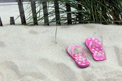 Flip flops. Pink with white polka dots sitting on the sandy dune near a weather fence with grass Stock Images