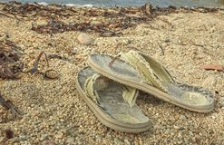 The flip-flops abandoned on the beach. Pair of worn and worn flip-flops abandoned on the sand of the Mediterranean beach stock images