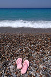 Flip-flops at the beach. An image of flip-flops at the beach with pebble stones Stock Photography