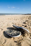Flip flops on the beach. Pair of flip flops on a beach, clear skys and a little surf Royalty Free Stock Photography