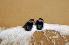 Flip-flops on the Beach. A pair of flip-flops in the water foam on the beach Royalty Free Stock Photos