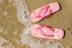 Flip flops at the beach. A pair of pink flip flops at the beach Royalty Free Stock Images