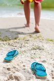 Flip-flops on beach. Woman going for a swim on a beach. Focus on shoes royalty free stock photos