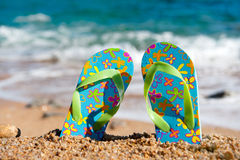 Flip flops at the beach. Colorful flip flops at the summer beach Royalty Free Stock Photos