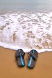 Flip flops at the beach. Pair of flip flops at the beach about to be washed away by the tide Royalty Free Stock Images