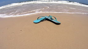 Flip Flops On Beach. Wave comes in and washes a pair of flip flops under the camera and back out again stock footage