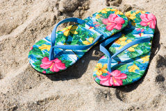 Flip flops on the beach. A pair of colorful and tropical flip flops on the beach Royalty Free Stock Image