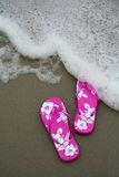 Flip-flops on the beach. Pink flip-flops on the sand at the beach as a wave approaches stock photos