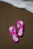 Flip-flops on the beach. Pink flip-flops on the sand at the beach as a wave approaches stock images