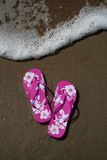Flip-flops on the beach. Pink flip-flops on the sand at the beach as a wave approaches royalty free stock photo