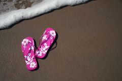 Flip-flops on the beach. Pink flip-flops on the sand at the beach as a wave approaches royalty free stock image