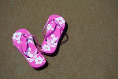 Flip-flops on the beach. Pink flip-flops on the sand at the beach stock image