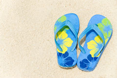 Flip Flops on the Beach. A pair of colorful flip flops on a sandy beach royalty free stock photo