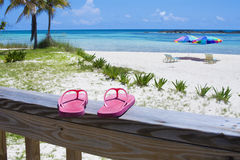 Flip flops on the beach. Pink Flip flops on the deck of a Caribbean beach resort. Beach umbrellas, palm trees, white sand and aqua-blue waters in the background Stock Photo