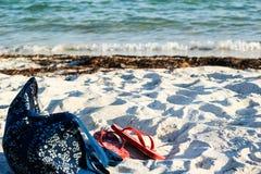 Flip flops and a beach bag on white sand Stock Photos