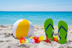 Flip flops and beach ball by the sea Royalty Free Stock Photos