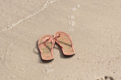 Flip-flops on a beach. Cute flip-flops on a beach Royalty Free Stock Image