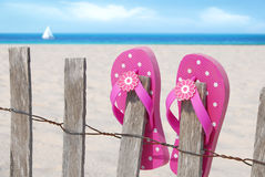 Flip flops on beach fence