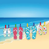 Flip flops on beach. Four pairs of flip flops hanging on a line on a beach Stock Image