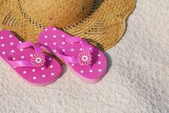 Flip flops on beach hat. Pretty pink flip flops on beach hat resting on sand royalty free stock images