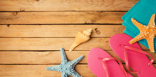 Flip flops with beach items on wooden deck background. View from above Stock Photos