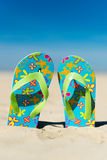 Flip flops at the beach. Pair colorful flip flops at the beach Royalty Free Stock Photography