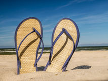 Flip-flops on the beach. Pair of straw flip-flops stuck into beach sand over blue sky stock photo