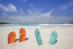 Flip-flops at the beach. Travel background with two pairs of flip-flops at a tropical beach stock photos