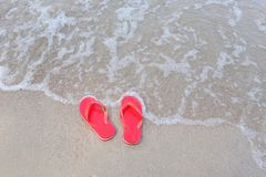 Flip flops on beach with wave sandy beach sea at the ocean stock photography