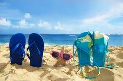 Flip flops, bikini and starfish with sunglasses on sandy beach. Flip flops with bikini and starfish with sunglasses on sandy beach with adult and couple in the Stock Image