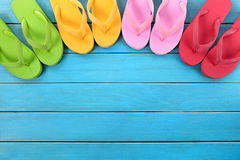 Flip flops with blue decking. Semi circle of colorful flip flops on old weathered blue painted beach decking. Space for copy royalty free stock photos