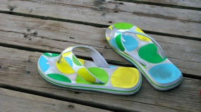 Flip flops on the boardwalk. A pair of bright polka dot flip flops on a wooden boardwalk royalty free stock images