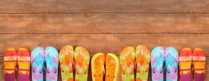 Flip-flops brilhantemente coloridos na madeira imagem de stock
