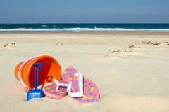 Flip-flops, bucket & spade. Colorful flip-flops, orange bucket and blue spade on sunny sandy beach background Stock Photos