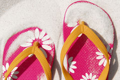 Flip flops buried in beach sand. Pair of pretty pink flip flops covered with fine beach sand stock photos