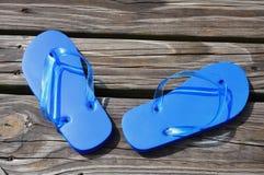 Flip Flops. Child's blue flip flops sitting on a boardwalk Royalty Free Stock Photography