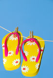 Flip Flops on Clothes Line. Colorful floral flip flop sandals hanging from clothes pins on a line Royalty Free Stock Photography