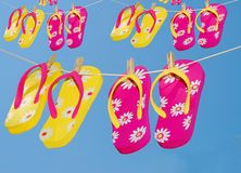 Flip Flops on clothes lines. Multiple pairs of colorful flipflops hanging on clothes lines Stock Photos