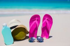Flip flops, coconut, hat and suncream on white Royalty Free Stock Photos