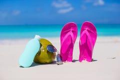 Flip flops, coconut and suncream on white sand Stock Image