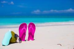 Flip flops, coconut and suncream on white sand Stock Photo