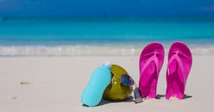 Flip flops, coconut and suncream on white sand Royalty Free Stock Image