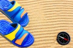 Flip-flops and compass on sand beach. Stock Photos