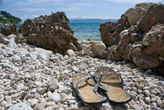 Flip-flops on the Croatian stone beach Royalty Free Stock Images