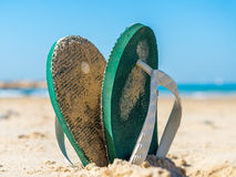 Flip flops. Digged into sand on the beach stock photography
