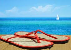 Flip Flops on Dock. Straw flipflops on oceanside dock with sailboat in distance stock photos