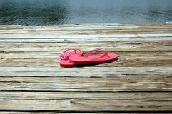 Flip flops on dock. Pink flip flops and flowers on dock by the lake royalty free stock photos